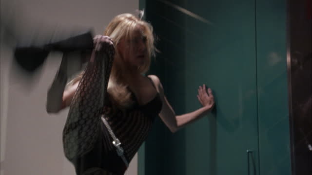 vidéos et rushes de zoom in on blond female go-go dancer in fishnet stockings dancing in glass cage. shot blurs out as it zooms in closer on  dancer. could be used for nightclub or strip club in north beach, san francisco. - peep show