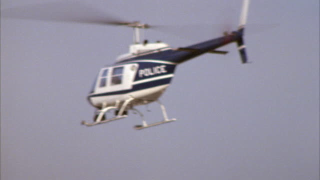 tracking shot of police helicopter flying in blue sky. helicopter flies from right to left, then circles and flies to right. - helicopter stock videos & royalty-free footage