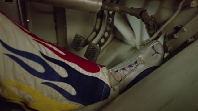 CLOSE ANGLE OF FOOT PRESSING GAS PEDAL, BRAKE PEDAL IN RACE CAR.  DRIVER WEARING JUMPSUIT WITH FLAME DESIGN. RACES, RACING.