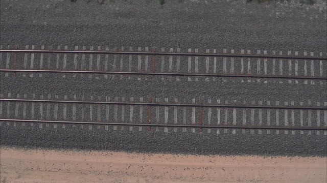 aerial of pair of parallel train tracks atop gray gravel. see shrubs and dirt flanking gravel. see wooden crossbars obscured by gravel. pan up to view just top tracks and shrubs in dirt at top. - top video stock e b–roll