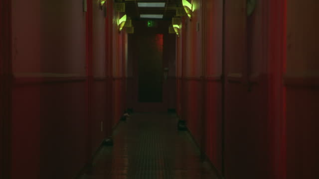 medium angle of hallway lit in pink lights.  could be a brothel, massage parlor, cheap hotel or motel. corridors. - bordell stock-videos und b-roll-filmmaterial