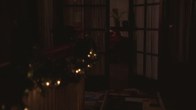 MEDIUM ANGLE OF BANISTER AND OPEN FRENCH DOORS IN HALLWAY. HOME IS UPPER TO MIDDLE CLASS. BANISTER DECORATED WITH CHRISTMAS LIGHTS AND GARLAND. BEDROOM VISIBLE THROUGH DOORS.