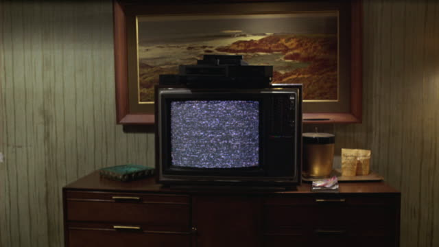 MEDIUM ANGLE OF TELEVISION SET ON COUNTER IN LOWER CLASS HOTEL OR MOTEL ROOM. STATIC ON SCREEN.