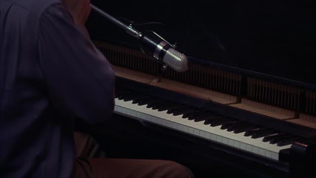 vídeos y material grabado en eventos de stock de close angle of a pianist playing the piano in a recording studio.  an old fashioned microphone hangs above the keys. instruments, musicians, music. - tiempo real grabación