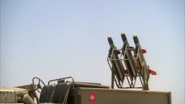 vidéos et rushes de medium angle of a military jeep with three missiles loaded in launcher. see each of the missiles launch one by one. middle east. - missile