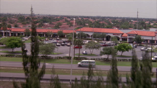 stockvideo's en b-roll-footage met aerial of forest grounds connecting to residential area with tract houses in blocks divided by streets. beauty shot. - miami