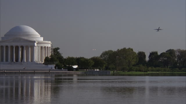 vidéos et rushes de medium angle of jefferson memorial on left with lake or reflecting pool in foreground. see trees on right. - jefferson memorial