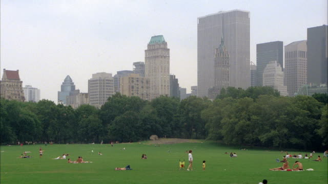 MEDIUM ANGLE OF THE GREAT LAWN IN CENTRAL PARK. SEE PEOPLE LOUNGING OR SUNBATHING ON GRASS. SEE TREES AND BUILDINGS IN BACKGROUND.