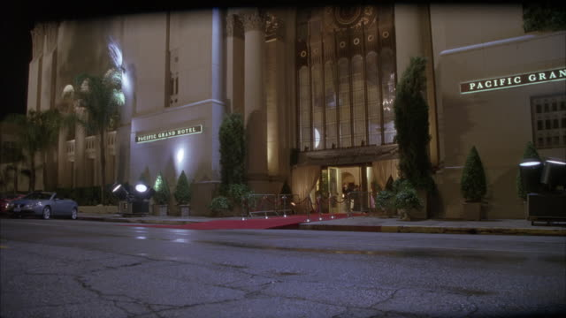 pan up of front entrance and facade of  park plaza hotel sign reads pacific grand hotel. camera pans right to left along side of hotel and returns focus to front entrance. banner that reads bridgeport senior high prom visible. - premiere stock videos & royalty-free footage