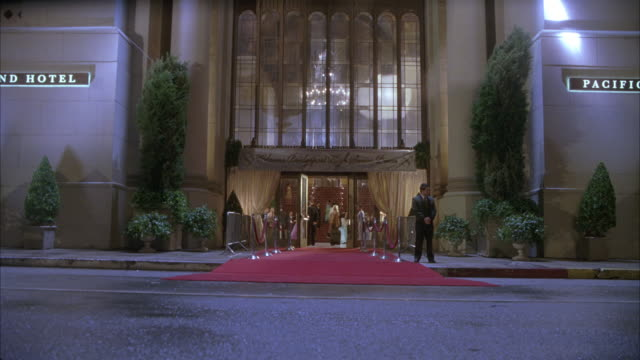 vidéos et rushes de wide angle of park plaza hotel sign reads pacific grand hotel front entrance. red carpet visible and valet standing outside doors as black car drives by. spotlights. could be used for movie premiere. - tapis rouge