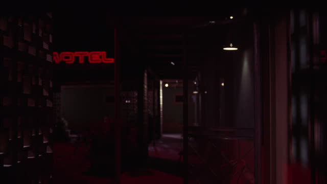 wide angle of dimly lit hotel hallway. lower class motel or hotel rooms. sign reading motel or hotel. - hotel room stock videos & royalty-free footage