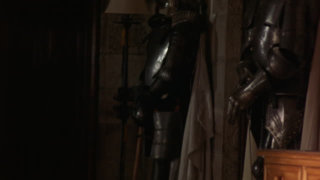 MEDIUM ANGLE OF TWO STATUES OF KNIGHTS WEARING METAL ARMOR IN CORNER OF ROOM. COULD BE UPPER CLASS MANSION, MANOR, OR ESTATE.