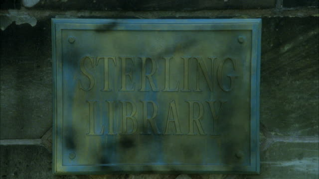 CLOSE ANGLE OF METAL SIGN MOUNTED ON STONE BACKGROUND READING STERLING LIBRARY. SEE MAN WALK PAST SIGN.