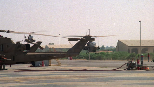 medium angle of two cobra military helicopters flying from behind helicopters lined on runway to right. airbase in background as helicopters exit frame to right. middle east. attack helicopters. - kampfhubschrauber stock-videos und b-roll-filmmaterial