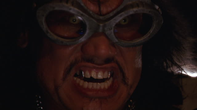 CLOSE ANGLE OF GROWLING OR SCREAMING MAN WITH METAL FANGS, GOGGLES.