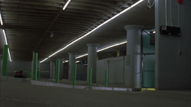 medium angle of parking structure or garage. see green metal poles, concrete columns rising to ceiling, and lights illuminated on ceiling. see blue gmc suv drive over curb inside garage and knock over green metal poles before driving out of frame. - multi storey stock videos & royalty-free footage