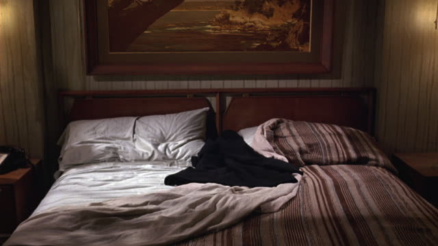 medium angle of bed in lower class hotel or motel room. man's jacket laying on bed. clothing. - hotel room stock videos & royalty-free footage