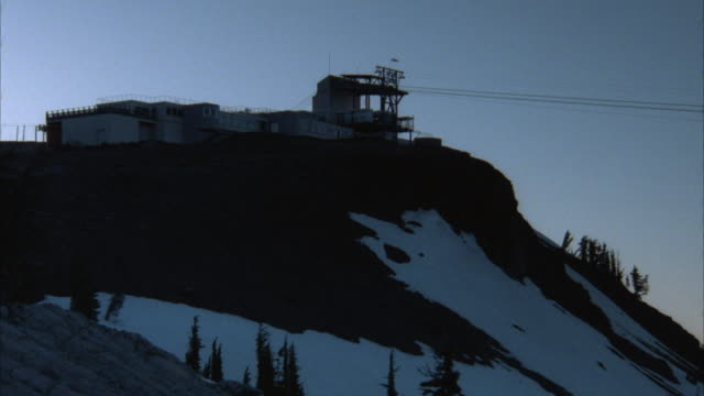 MEDIUM ANGLE OF A MOUNTAIN WITH PATCHES OF SNOW ON THE SIDE. AERIAL CABLE CAR STATION AND WIRES ON TOP OF THE MOUNTAIN. SEE LIGHT SHINING FROM LEFT.