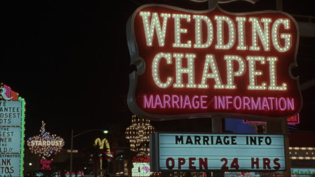 MEDIUM ANGLE OF NEON SIGN THAT READS WEDDING CHAPEL MARRIAGE INFORMATION - MARRIAGE INFO OPEN 24 HRS. NEON LIGHTS IN BACKGROUND. NEG CUT.