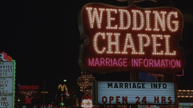 medium angle of neon sign that reads wedding chapel marriage information - marriage info open 24 hrs. neon lights in background. neg cut. - information sign stock videos & royalty-free footage