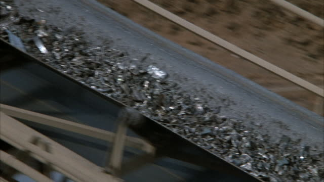 CLOSE ANGLE OF UPWARD RAMP BELT CARRYING METAL PIECES. SHOT TRACKS METAL PIECES MOVING ON RAMP TOWARD TOP LEFT AND STOP AT TOP WHEN METAL PIECES FALL OFF RAMP.