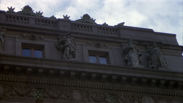 UP ANGLE OF BUILDING OR HOTEL, COULD BE OFFICE BUILDING. BAS RELIEF STATUES ON BUILDING NEXT TO WINDOWS.