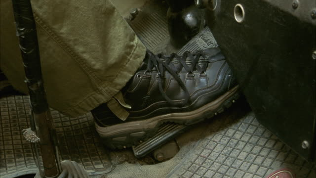 MEDIUM ANGLE OF MAN'S SNEAKER PRESSING DOWN ON GAS AND BRAKE PEDALS IN TRUCK. BRAKING HARD. INSERT.