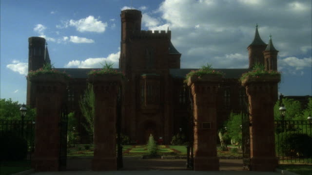 vídeos de stock, filmes e b-roll de medium angle of smithsonian and front courtyard garden. see four pillars and gate in front. see clouds. - smithsonian institution