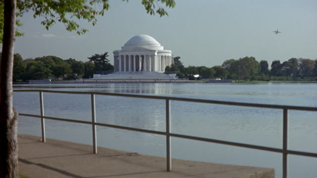 stockvideo's en b-roll-footage met medium angle of jefferson memorial behind reflecting pool and railing in foreground. commercial airliner flies in distance at right. - memorial