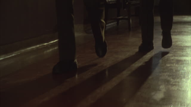 hand held tracking shot of the legs of two men in dark pants, probably cops or police officers, walking down a long dimly lit hallway. could be an apartment or an office. - corridor stock videos & royalty-free footage