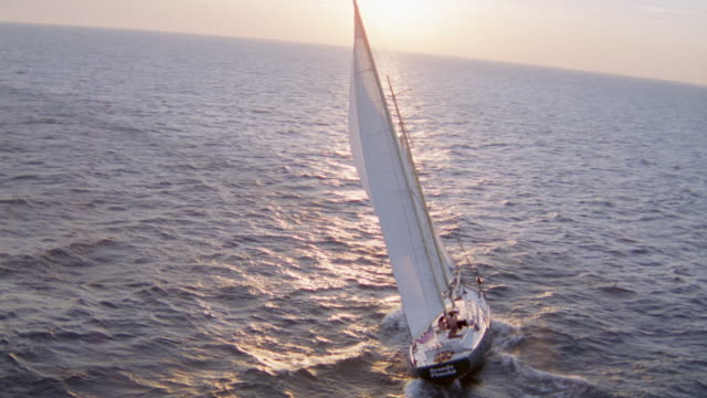 AERIAL OF LARGE SAILBOAT WITH WHITE SAILS. SEE BOAT SAILING TOWARDS HORIZON. SUNLIGHT IS REFLECTED ON WATER.