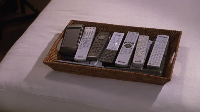 CLOSE ANGLE OF A BOX OF REMOTE CONTROLS ON A WHITE BED OR CHAIR.  LOOKS LIKE A BEDROOM OR A NICE HOTEL ROOM.