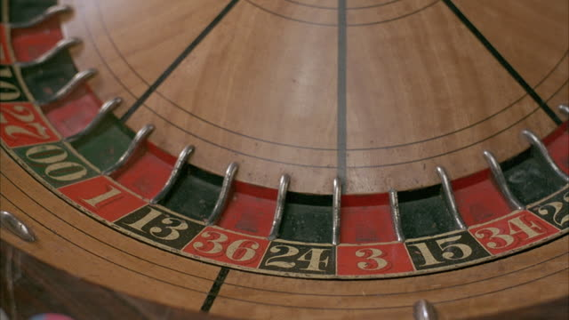 close angle of roulette wheel, probably in casino. croupier's hand reaches in from right with ball in hand and spins wheel. insert. filter changes at start of shot. - casino stock videos & royalty-free footage