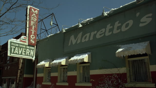 stockvideo's en b-roll-footage met up angle of restaurant. signs reads maretto's and italian cuisine sea food tavern. snow, probably winter. - bar gebouw
