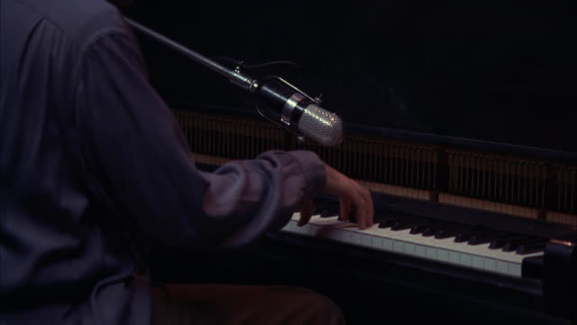 vidéos et rushes de close angle of a pianist playing the piano in a recording studio.  an old fashioned microphone hangs above the keys. instruments, musicians, music. - studio d'enregistrement
