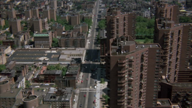 AERIAL OVER CITY WITH SEVERAL BRICK-COLORED BUILDINGS. SEE HIGH RISE APARTMENT COMPLEXES. VIEW OF DISTANT BODY OF WATER. FOLLOWS ALONG MAIN STREET PASSING THROUGH CITY.