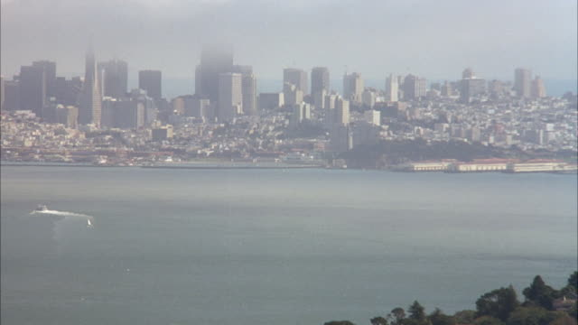 aerial pull back of san francisco skyline by bay and cities. beauty shot. - baia di san francisco video stock e b–roll