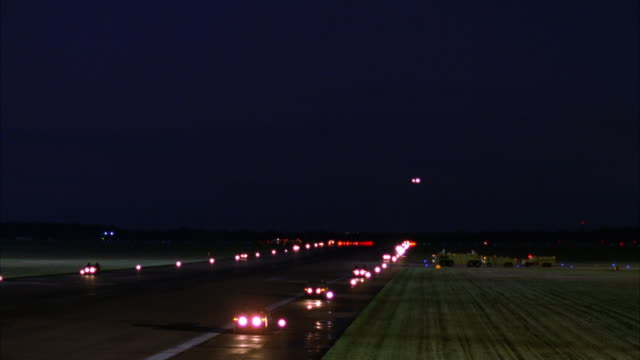 MEDIUM ANGLE OF LIT RUNWAY AT NIGHT. SEE AIR FORCE ONE AIRPLANE APPEAR FROM DISTANCE, DESCEND AND FLY PAST RUNWAY TO LEFT.