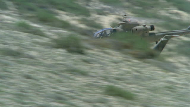 MEDIUM ANGLE TRACKING SHOT OF TWO COBRA MILITARY HELICOPTERS FLYING LOW TO GROUND. HELICOPTERS APPEAR FROM RIGHT AND DISAPPEAR BEHIND HILL. ONE HELICOPTER REAPPEARS AND EXITS FRAME TO LEFT. SAND AND BRUSHES IN BACKGROUND. MIDDLE EAST. ATTACK HELICOPTERS.