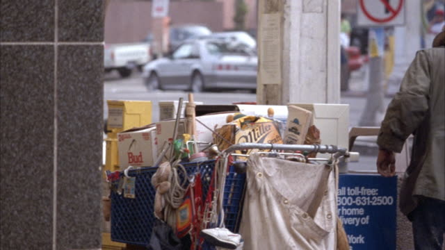 vídeos y material grabado en eventos de stock de medium angle of homeless man walking on street with shopping cart full of his belongings. he stops to rummage through garbage can on street corner. - 1990