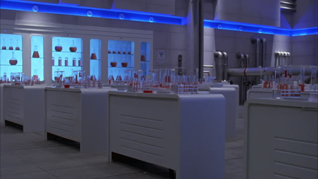 wide angle of interior of futuristic laboratory. see glass bottles and vials lined up on glass shelves in the wall. see blue glow of neon or other ceiling light. many glass bottles, flasks, and vials cover the white tables in the laboratory. - explosion wall stock videos and b-roll footage