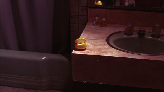 MEDIUM ANGLE OF SINK AND COUNTER TOP IN BATHROOM. SHOWER VISIBLE. APPLE WITH BLOOD ON IT SITTING ON COUNTER.