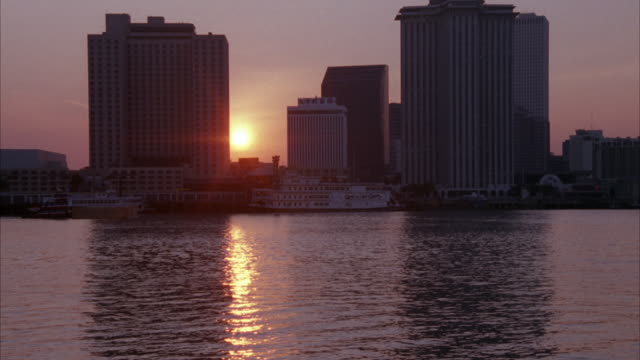 vídeos de stock, filmes e b-roll de wide angle of part of miami skyline from across river. see barge pass by to left. sun in between building in center. - 1995