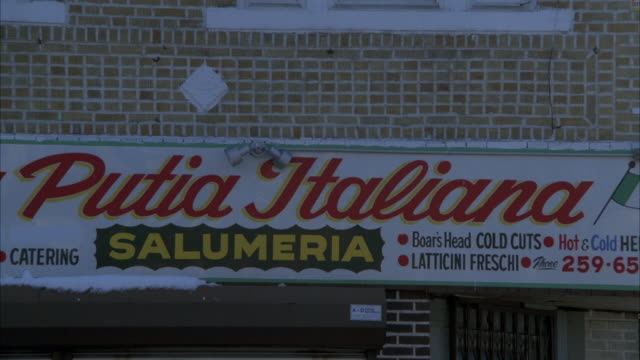 MEDIUM ANGLE OF SIGN FOR PUTIA ITALIANA RESTAURANT. PULLS BACK TO SEE STREET CORNER WITH CARS PARKED ALONG CURB. SEE SNOW ON SIDEWALK AND IN STREET. SEE CAR PARKED IN FRONT OF CLOSED RESTAURANT WITH ROLLED DOOR COVERING ENTRANCE.