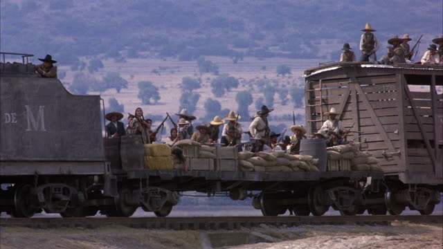 PAN LEFT TO RIGHT OF STEAM ENGINE TRAIN TRAVELING FROM RIGHT TO LEFT. SEE MEXICAN SOLDIERS ON ROOF OF TRAIN SHOOTING IN DIRECTION THE TRAIN IS MOVING. SEE DESERT IN BACKGROUND.