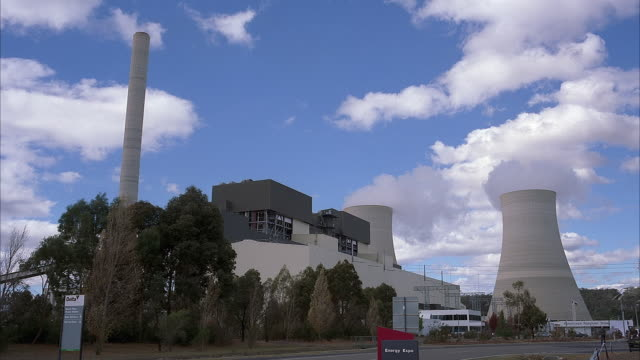 wide angle of nuclear power plant. see pair of cooling towers with steam rising from top. see white and gray multi-story building as part of power plant complex. blue sky with white clouds in background.  empty parking lot in foreground. - atomkraftwerk stock-videos und b-roll-filmmaterial