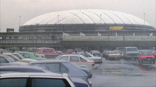 MEDIUM ANGLE OF BC PLACE STADIUM AND PARKING LOT. SEE CARS DRIVING BY ON FREEWAY IN FRONT OF STADIUM. RAINING.