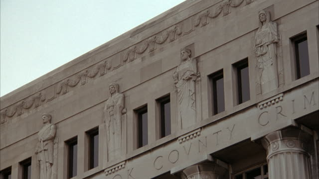 medium up angle of top of stone building with human figures carved into side. see part of words carved into building on bottom of screen. possibly courthouse or government building. cook county courthouse. - courthouse stock videos & royalty-free footage
