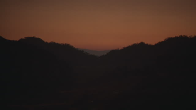 wide angle of mountains with valley, trees silhouetted against an orange sunset sky. - valley stock videos & royalty-free footage