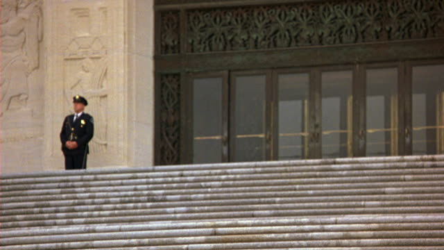 medium angle of front entrance of the capitol building in baton rouge, louisiana.  statues. stone steps. government buildings. shot starts by racking focus in to guard, and ends out of focus. - kapitol von louisiana stock-videos und b-roll-filmmaterial